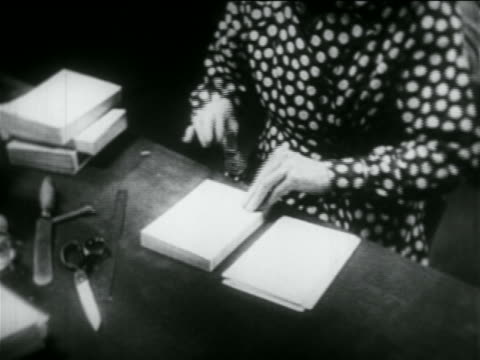 b/w 1934 close up hands of woman stamping books in library in wpa project / documentary - 図書館員点の映像素材/bロール