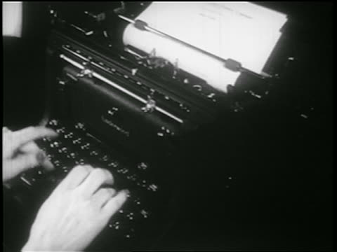 b/w 1939 close up hands of woman typing / documentary - タイプライター点の映像素材/bロール