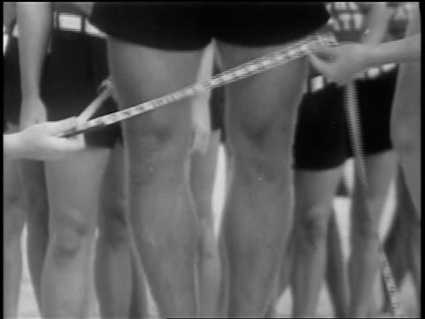b/w 1937 close up hands of women measuring legs of male lifeguard in beauty contest / florida / newsreel - beauty contest stock videos & royalty-free footage