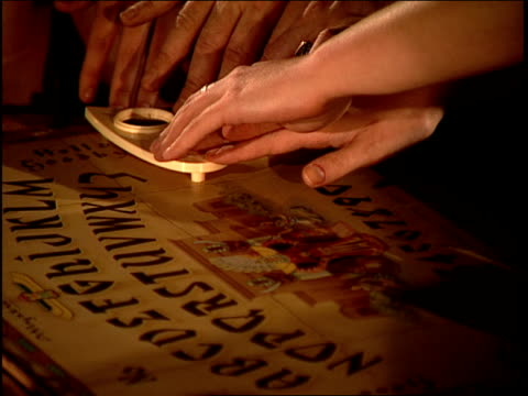 close up hands on planchette being used on ouija board - ghost stock videos & royalty-free footage