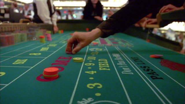 Close up hands placing bets and rolling dice at casino craps table / Las Vegas