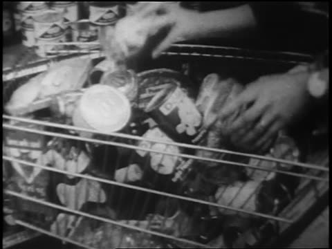 stockvideo's en b-roll-footage met b/w 1962 close up hands putting canned goods into full shopping cart during cuban missile crisis - koude oorlog