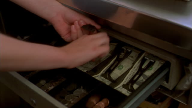 Close up hands taking money from cash register and handing change through window