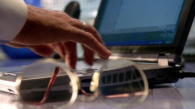 Close up hands typing on laptop / eyeglasses in foreground / left hand answering telephone in background