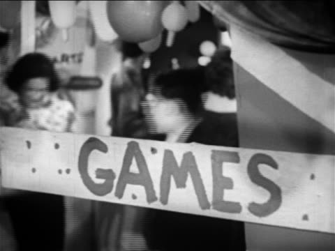 "b/w 1949 close up handwritten ""games"" sign attached to pole / people walking around in background / educational - school fete stock videos and b-roll footage"