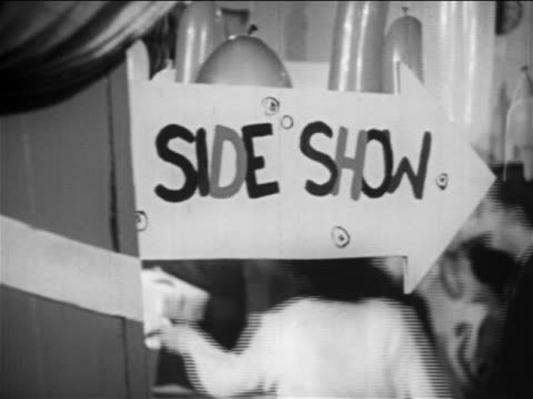 "vidéos et rushes de b/w 1949 close up handwritten ""side show"" arrow sign / teens walking in background / educational - 1949"