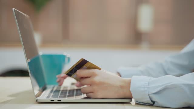 närbild happy asiatisk kvinna med laptop och kreditkort för online shopping - endast unga kvinnor bildbanksvideor och videomaterial från bakom kulisserna