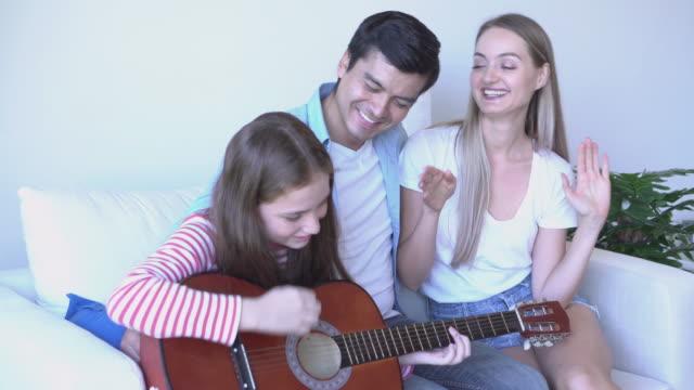 クローズアップ幸せな家族はリビングルームで音楽を楽しむ - living room点の映像素材/bロール