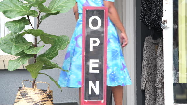 close up happy young boutique owner putting open sign outside store - store sign stock videos & royalty-free footage