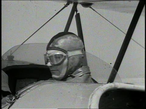 b/w 1941 close up head of pilot with goggles in open cockpit of bi-plane turning around / aero'nutics - プロペラ機点の映像素材/bロール