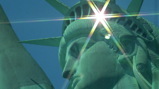 close up head of statue of liberty / sun reflecting in starburst off glass in crown - statue of liberty new york city stock videos and b-roll footage