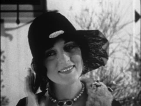 b/w 1929 close up head of woman modeling hat with lace brim outdoors / newsreel - 1920年点の映像素材/bロール