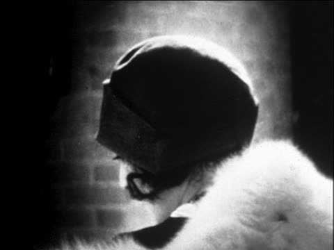 B/W 1929 close up head of woman modeling hat with puffball on one side outdoors / newsreel