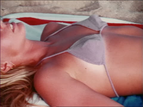 vídeos de stock, filmes e b-roll de 1969 close up pan head to legs of blonde woman in bikini lying on towel on beach / hawaii / travelogue - biquíni