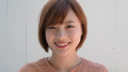 Close up headshot portrait of young Japanese woman opening eyes and smiling to camera smiling