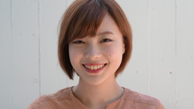 目を開け、笑顔でカメラに微笑む日本の若い女性のヘッドショットの肖像画をクローズアップ - 表す点の映像素材/bロール