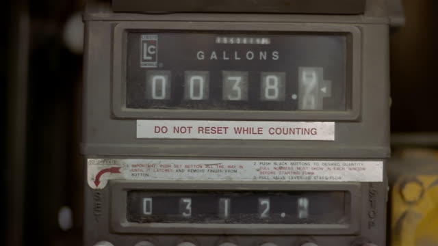 close up heating oil meter ticking off gallons - インフレ点の映像素材/bロール