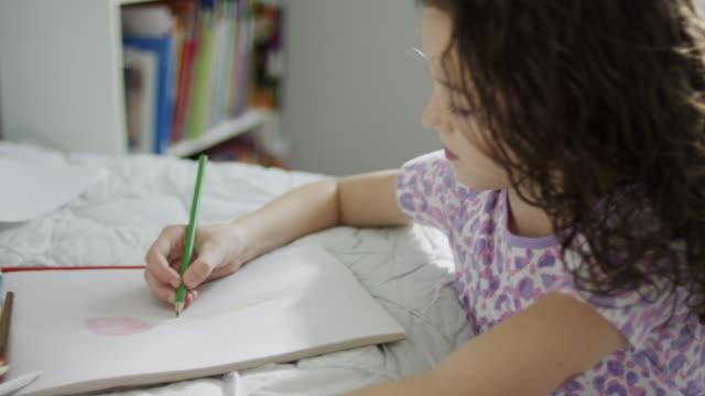 close up high angle panning shot of girl drawing on sketchpad / provo, utah, united states - provo bildbanksvideor och videomaterial från bakom kulisserna