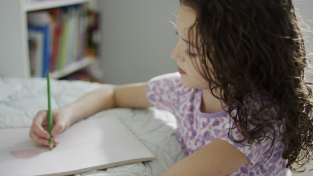 close up high angle panning shot of smiling girl drawing on sketchpad / provo, utah, united states - provo bildbanksvideor och videomaterial från bakom kulisserna