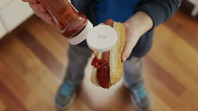 """close up high angle shot of boy squirting ketchup on hot dog / cedar hills, utah, united states"" - ketchup stock videos and b-roll footage"