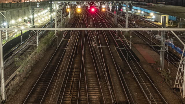 a close up high angle view looking down onto multiple railway tracks leading towards euston station during the evening rush hour as light trails of commuter trains rush by arriving and departing - 線路のポイント点の映像素材/bロール
