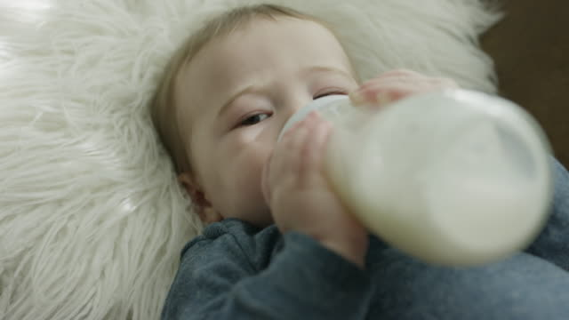 Close up high angle view of baby drinking from baby bottle / Provo, Utah, United States
