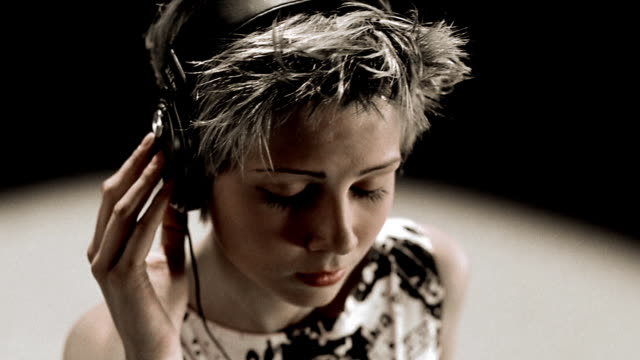 close up high angle woman with short blonde hair + eyes closed wearing headphones moving head to music