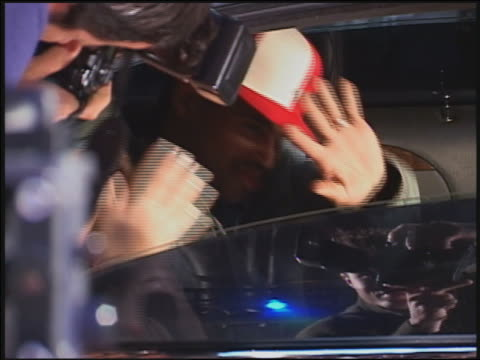 Close up hip hop stars shielding eyes from flashing cameras in back of limo / AUDIO