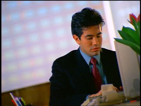vídeos de stock, filmes e b-roll de close up hispanic businessman working at desk in office / woman talks to him + he makes phone call - vestuário de trabalho formal