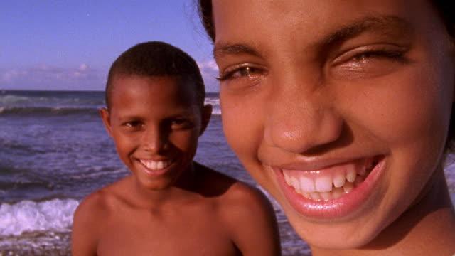 close up hispanic girl and boy posing and smiling on beach / dominican republic - ドミニカ共和国点の映像素材/bロール