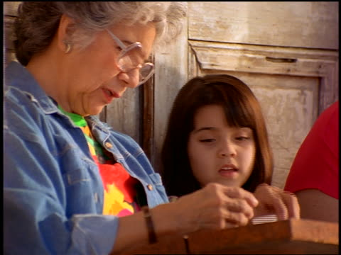 close up Hispanic girl + grandmother looking at photographs in box outdoors
