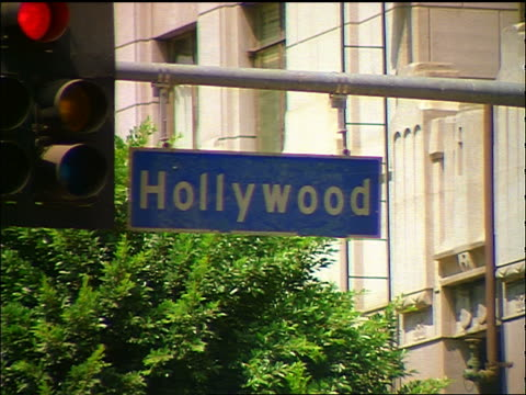close up hollywood street sign next to changing traffic light / los angeles - hollywood los angeles stock-videos und b-roll-filmmaterial