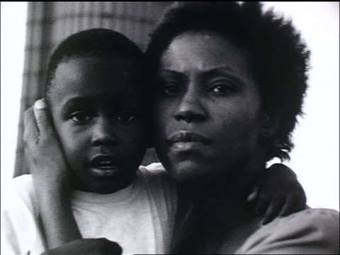 b/w close up homeless black woman holding son + looking at camera / zoom out to dump - boys stock videos & royalty-free footage