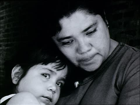 B/W close up homeless Hispanic woman holding daughter