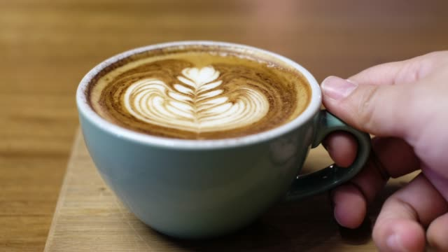 close up hot cappuccino coffee cup with latte art on wood table and lift up to drink in coffee shop - coffee cup stock videos & royalty-free footage