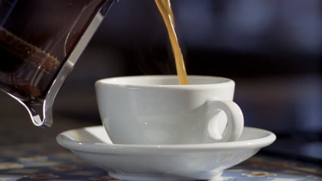 close up hot coffee being poured from french press into coffee cup with saucer - saucer stock videos and b-roll footage