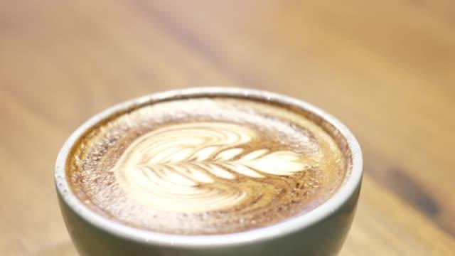 vídeos de stock, filmes e b-roll de fechar a xícara de café quente com latte art na mesa de madeira em loja de café - madeira