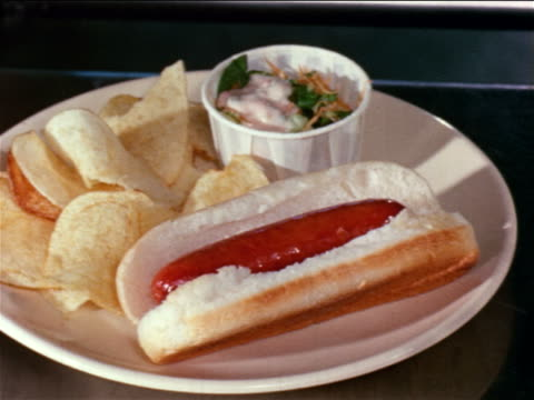 1964 close up hot dog, potato chips + small salad on dish / educational - crisps stock videos & royalty-free footage