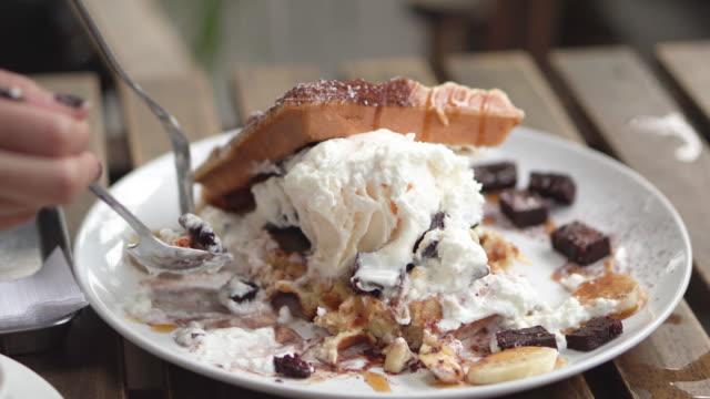 vídeos y material grabado en eventos de stock de cerrar humano comiendo waffle de helado de postre. - gofre belga