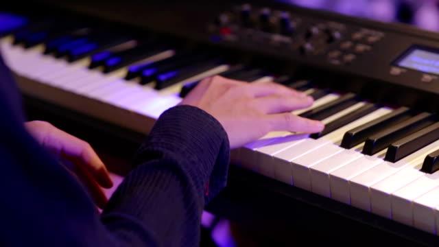 nahaufnahme der menschlichen hand spielt klavier am konzert-party - griffbrett stock-videos und b-roll-filmmaterial