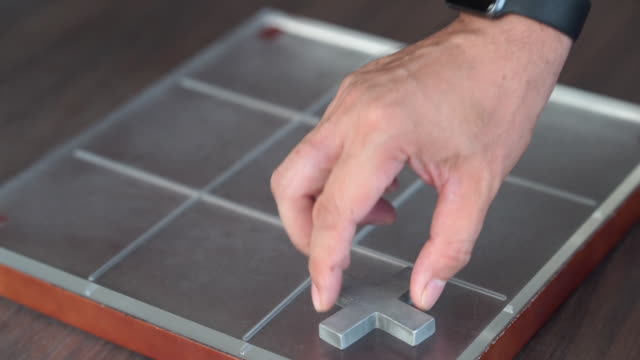 nahaufnahme , menschliche hand spielen tic-tac-toe-spiel - kreuz religiöser gegenstand stock-videos und b-roll-filmmaterial