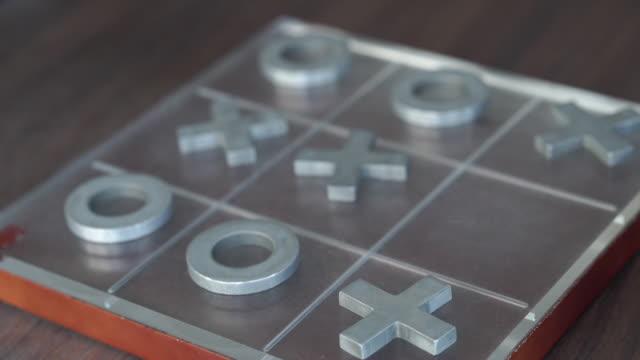 vídeos de stock e filmes b-roll de close up , human hand playing tic-tac-toe game - jogo do galo