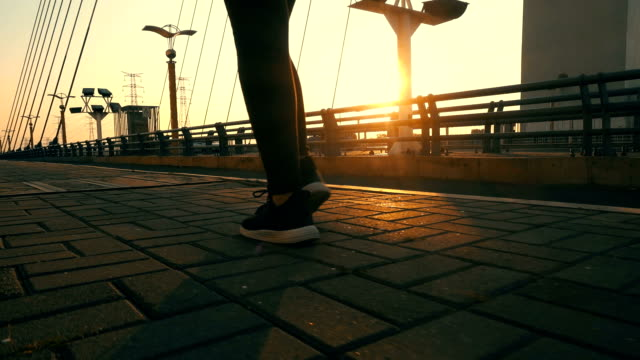 close up human leg walking on a bridge with sunlight - human foot stock videos and b-roll footage