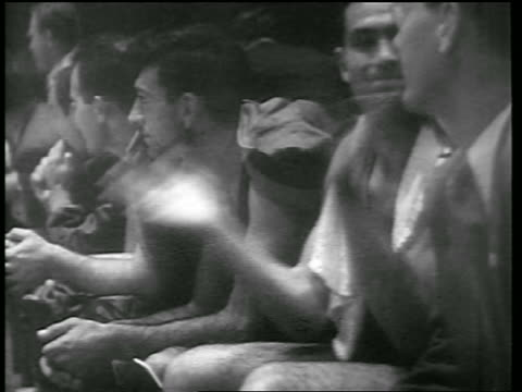 vídeos de stock, filmes e b-roll de b/w 1946 close up huskies players sitting on bench clapping in game vs ny knicks / news - 1946