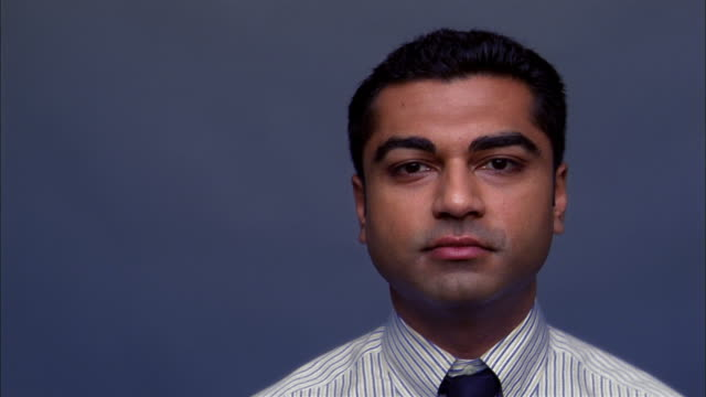 Close up Indian man in shirt and tie looking at CAM seriously