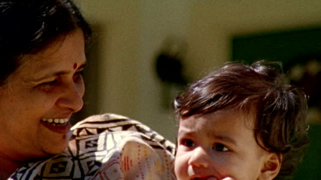 Close up Indian woman holding baby and smiling