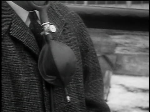 b/w 1939 close up inflating + deflating bag of oxygen mask worn by man (man's head not visible) - oxygen mask stock videos & royalty-free footage