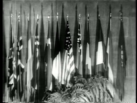 b/w 1949 close up international flags indoors at united nations / documentary - 1949 stock-videos und b-roll-filmmaterial