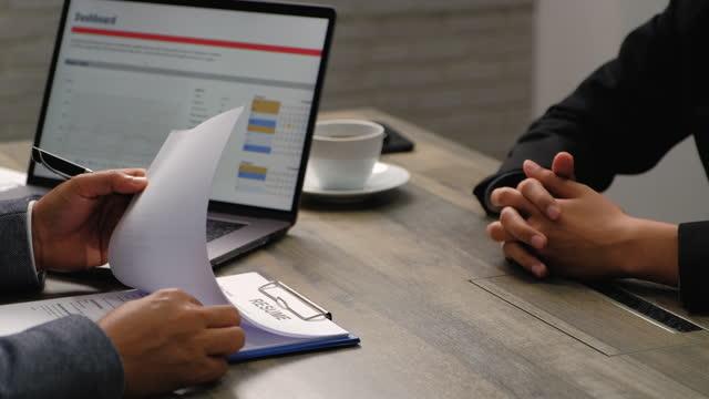 面接官面接候補者をクローズアップし、オフィスの会議室での仕事に応募する際に履歴書を確認します。 - 合意点の映像素材/bロール