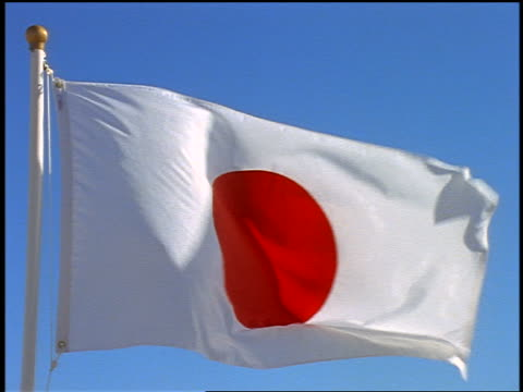 close up pan japanese flag blowing in wind / blue sky in background - japan flag stock videos & royalty-free footage